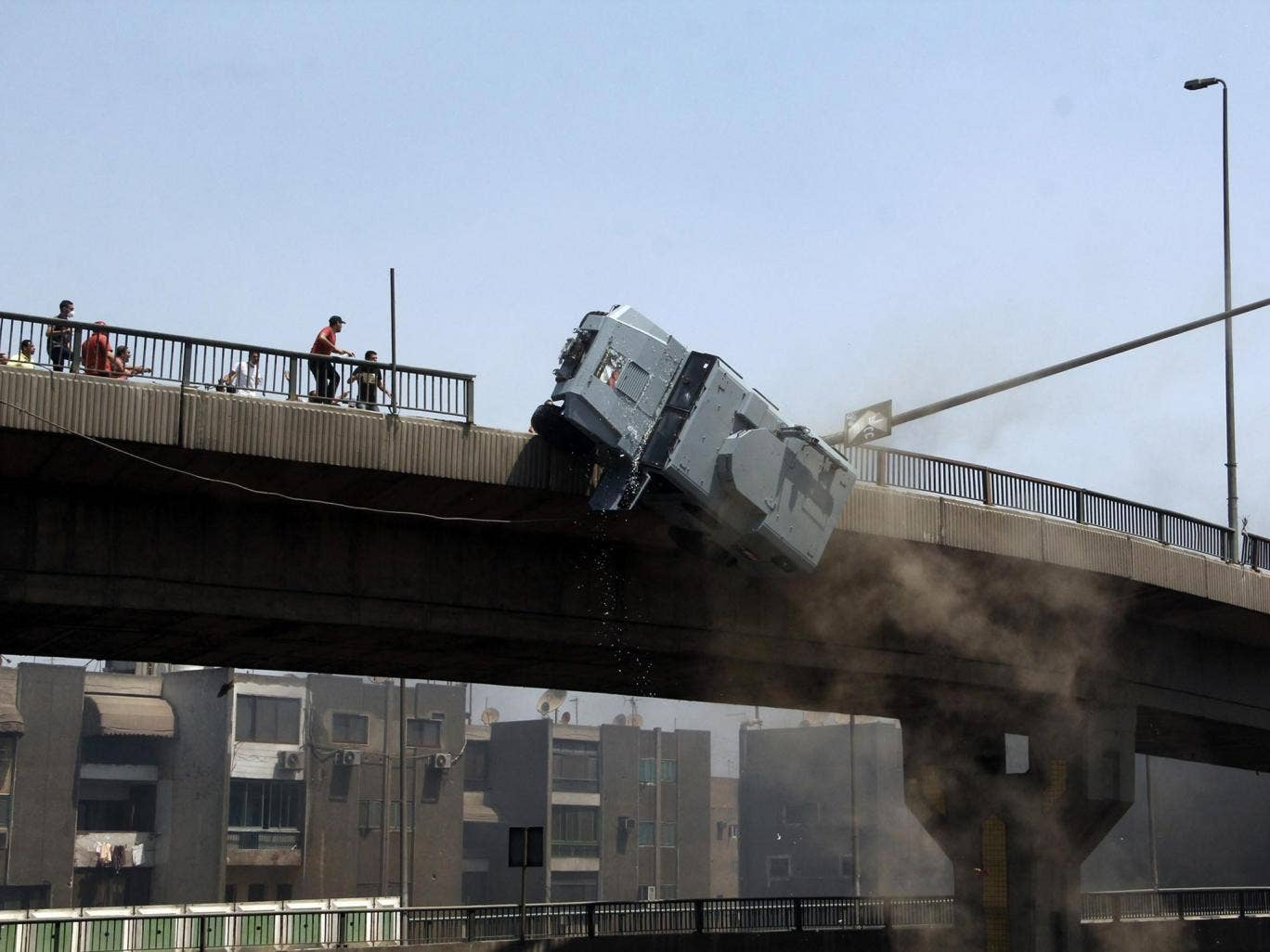 A police vehicle is pushed off the 6th of October bridge by protesters close to the largest sit-in by supporters of ousted Islamist President Mohammed Morsi in the eastern Nasr City district of Cairo, Egypt