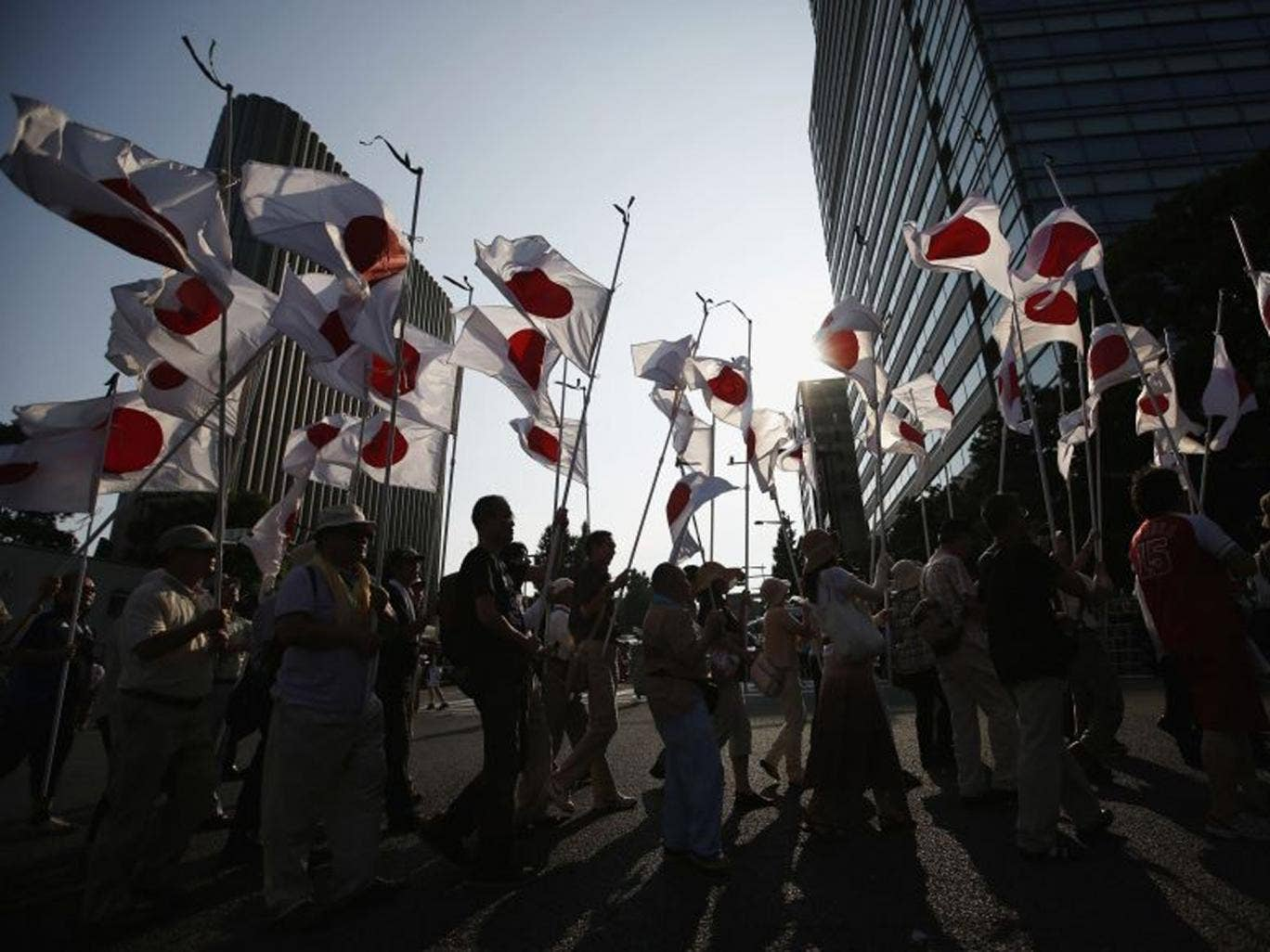 Members of nationalist movement 'Ganbare Nippon' march with Japanese national flags while paying tribute to the war dead near Yasukuni Shrine