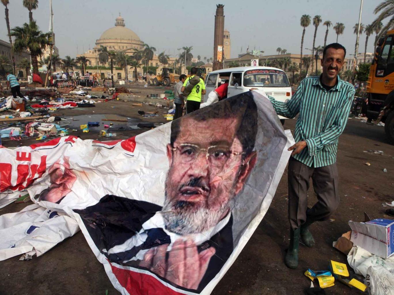 An Egyptian holds up a banner of Egypt's ousted President Mohamed Morsi in Cairo
