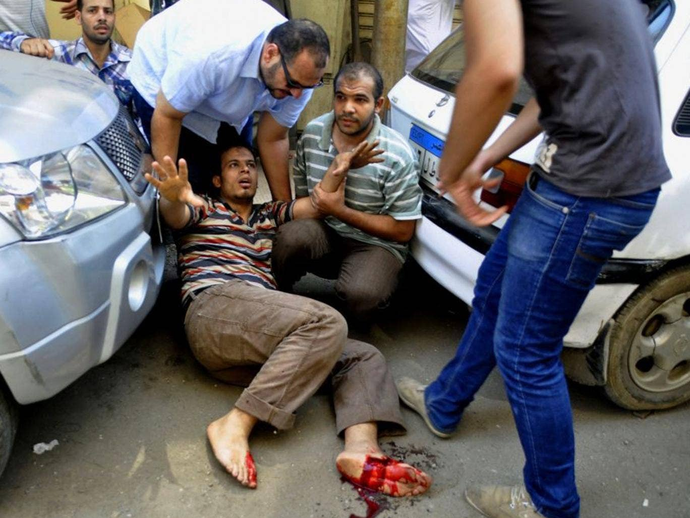 An Egyptian protester lies wounded after a Muslim Brotherhood protest approached a church protected by the army in Giza, Egypt on 16 August 2013