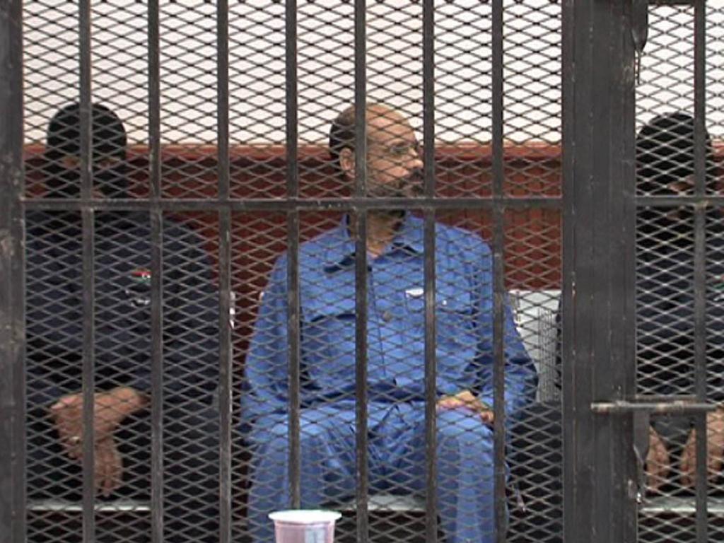 Saif al-Islam Gaddafi in a defendant's cage in a courtroom in Zintan