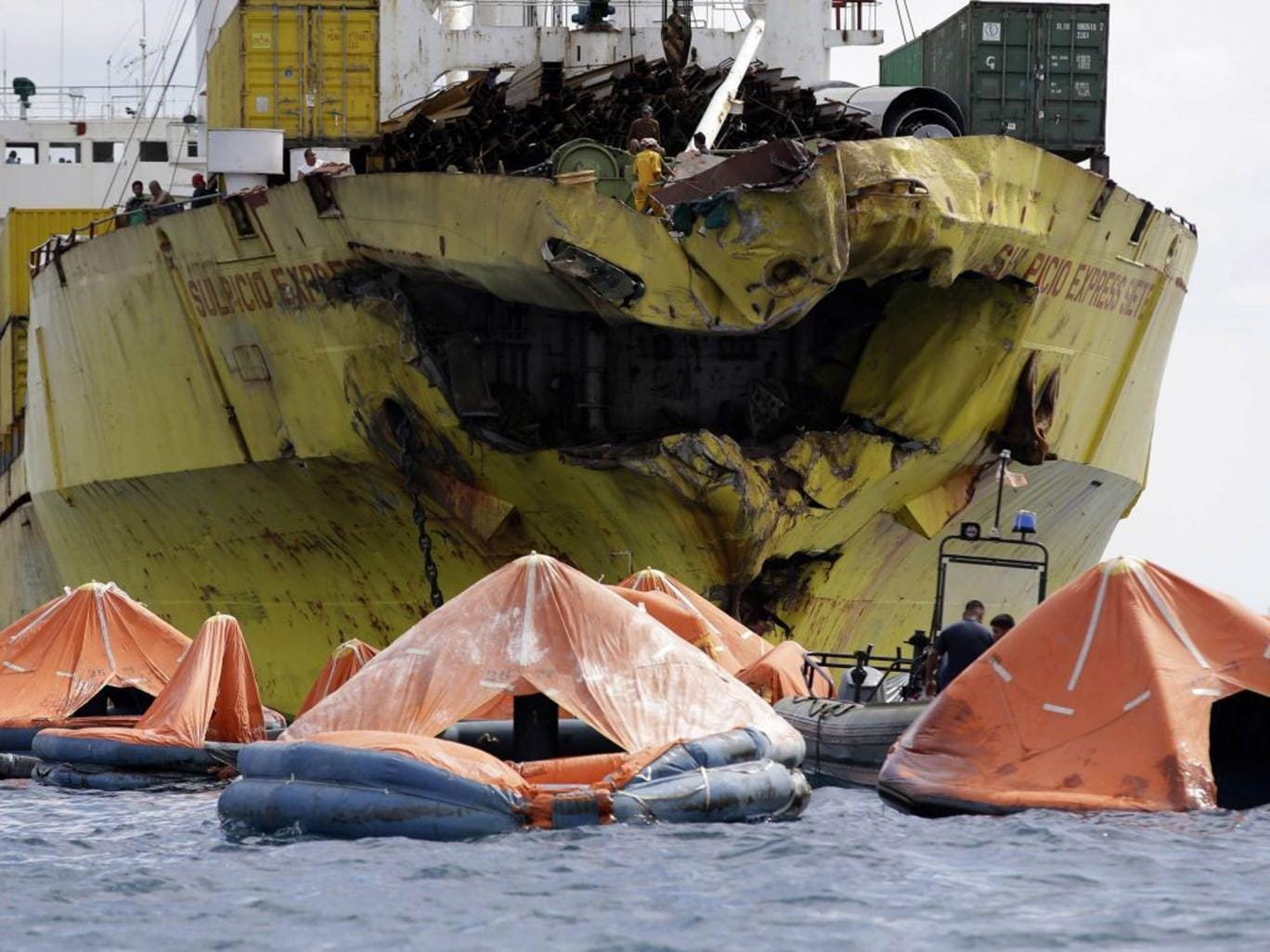 A cluster of life rafts floats near the cargo ship Sulpicio Express Siete Saturday Aug. 17, 2013, a day after it collided with a passenger ferry