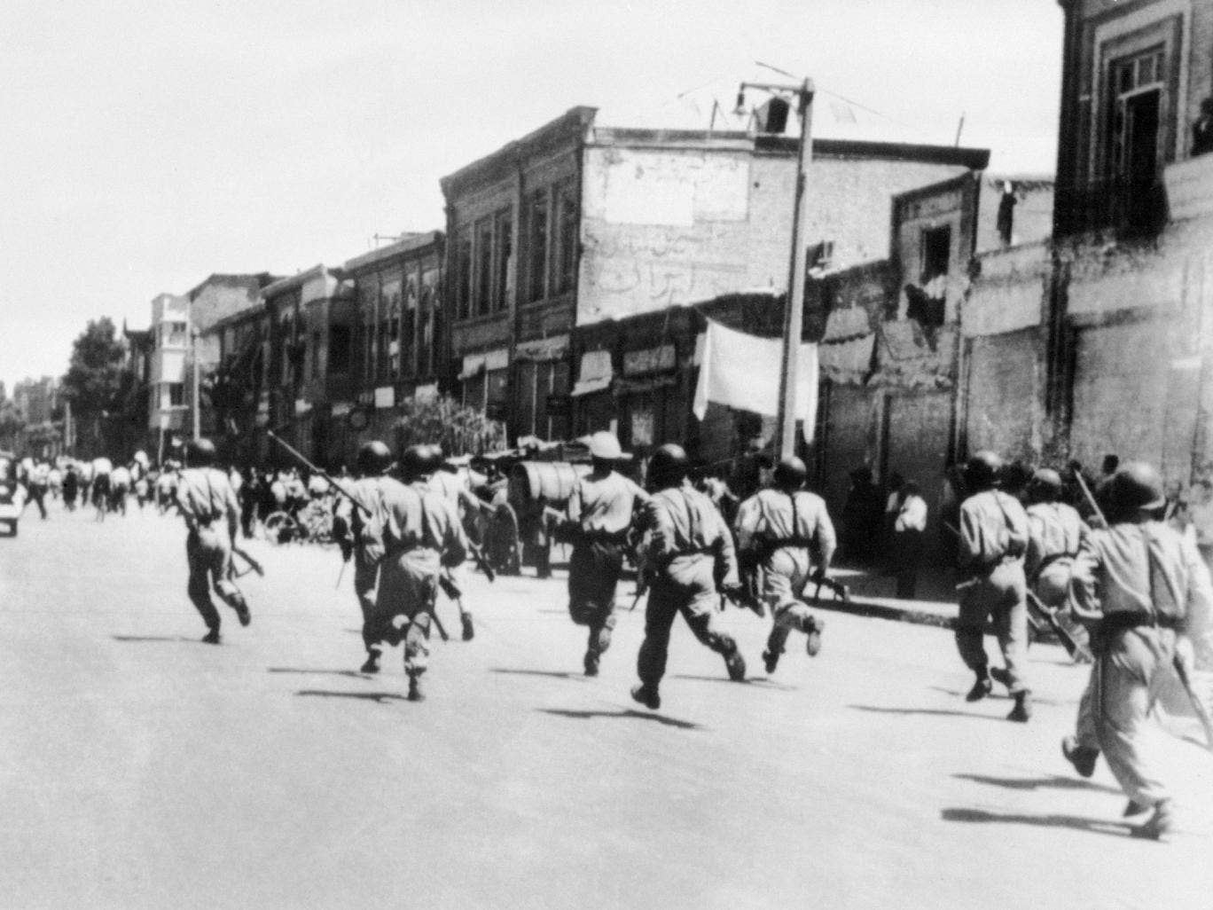 Persian soldiers chase rioters during civil unrest in Tehran, August 1953