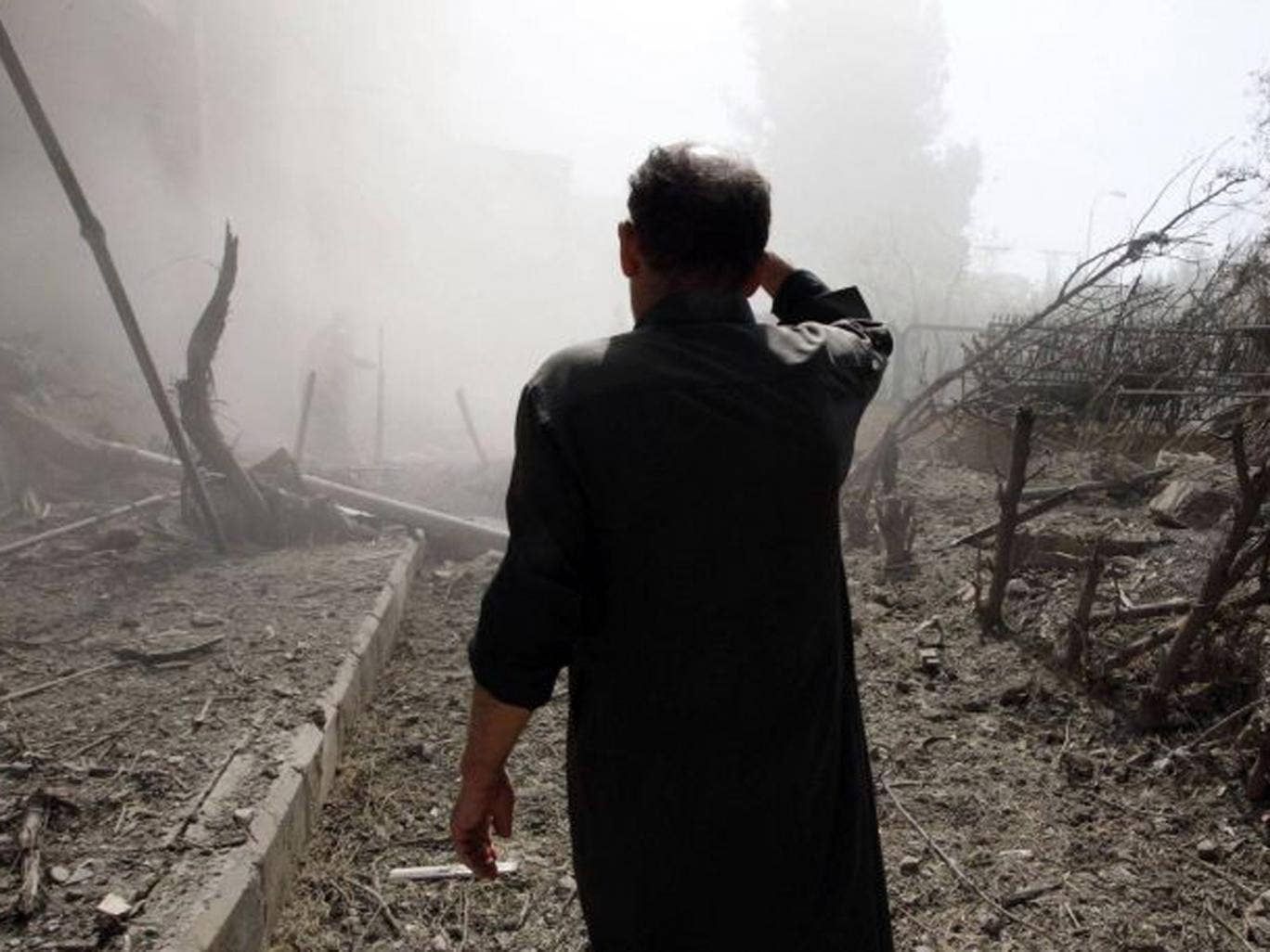 A man inspects a site hit by what activists said were missiles fired by Syrian Air Force fighter jets loyal to President Bashar al-Assad, in Raqqa province, eastern Syria  on 21 August 2013