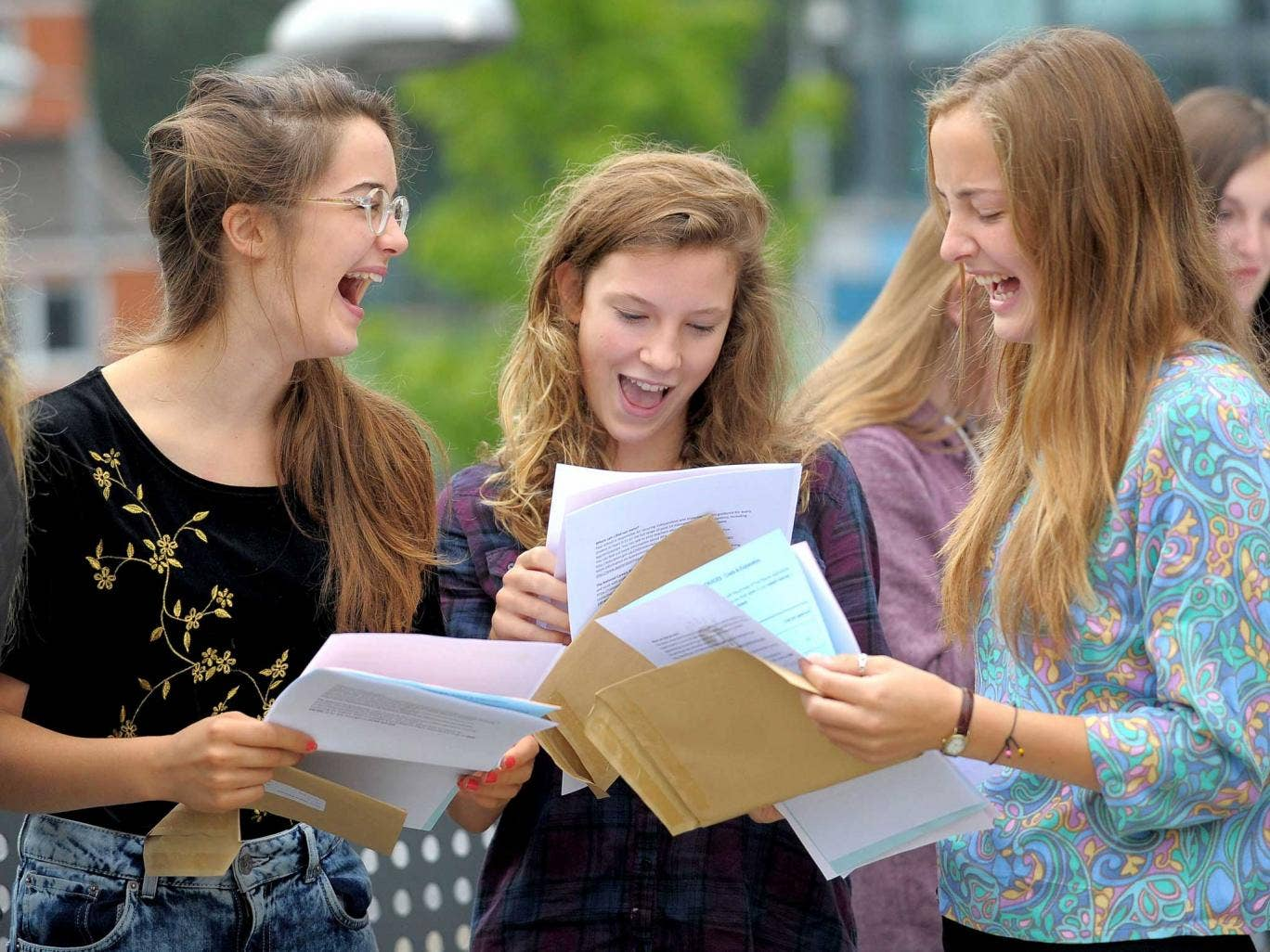 Charlotte Penn (centre) and twins Florence (left) and Dorothy Hislop (right) open their GCSE results at St Mary Redcliffe and Temple in Bristol