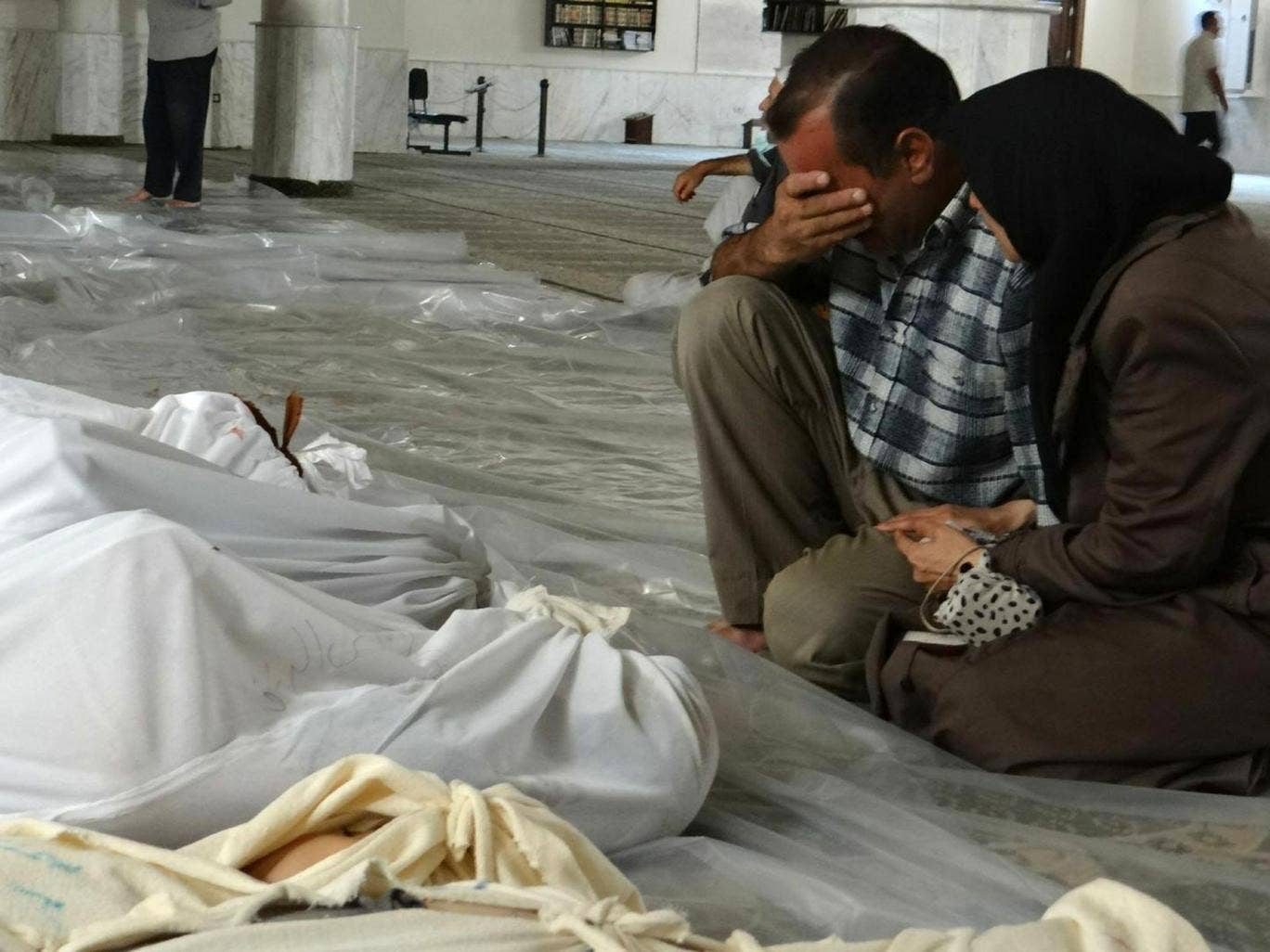 A Syrian couple mourning in front of bodies wrapped in shrouds ahead of funerals following what Syrian rebels claim to be a toxic gas attack by pro-government forces in eastern Ghouta, on the outskirts of Damascus