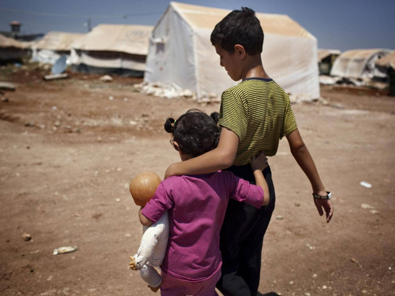 Syrian refugee children walk in the Bab al-Salam refugee camp in Syria's northern city of Azaz