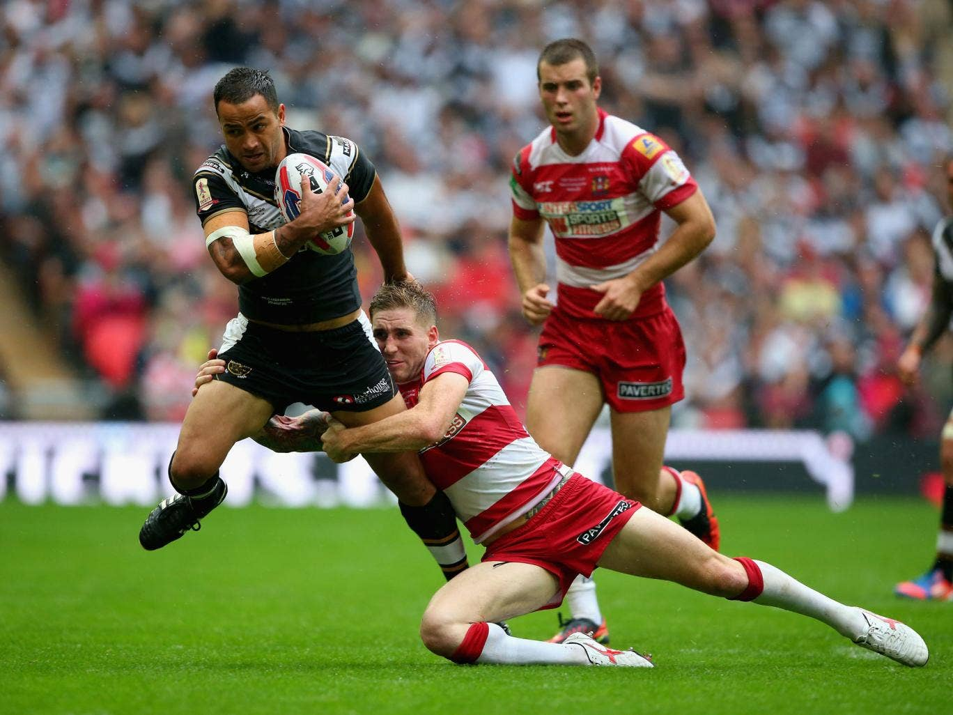 Sam Tomkins of Wigan Warriors tackles Aaron Heremaia of Hull FC