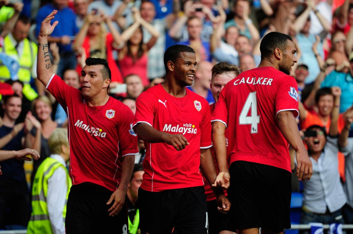 CARDIFF, WALES - AUGUST 25: Cardiff City scorers Fraizer Campbell (c) and team mates lead the celebrations after the third Cardiff goal during the Barclays Premier League match between Cardiff City and Manchester City at Cardiff City Stadium.