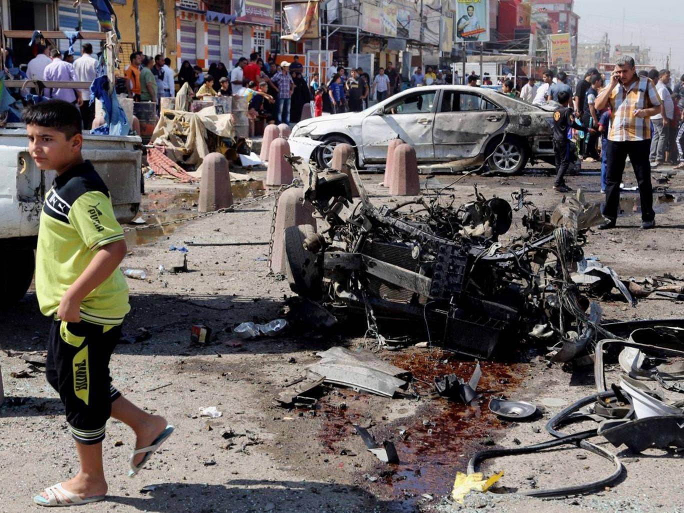 People inspect the site of a car bomb attack in Sadr City, Baghdad, as a co-ordinated wave of bombings tore through Shia Muslim areas in and around the Iraqi capital