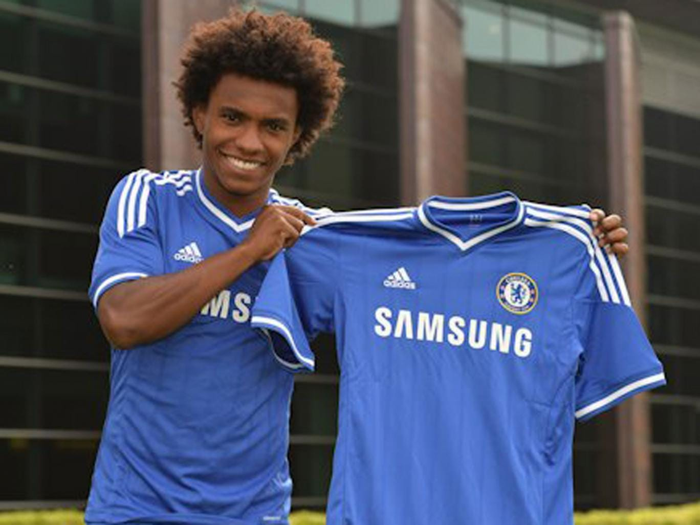 Willian holds the Chelsea shirt after completing his £32m move