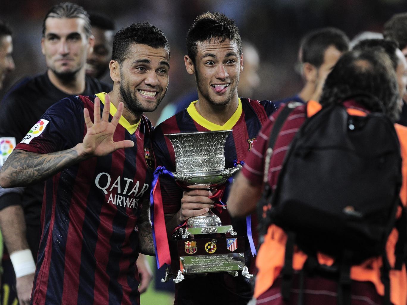 Barcelona's Brazilian defender Dani Alves (L) and Brazilian forward Neymar celebrate with the Spanish Super Cup