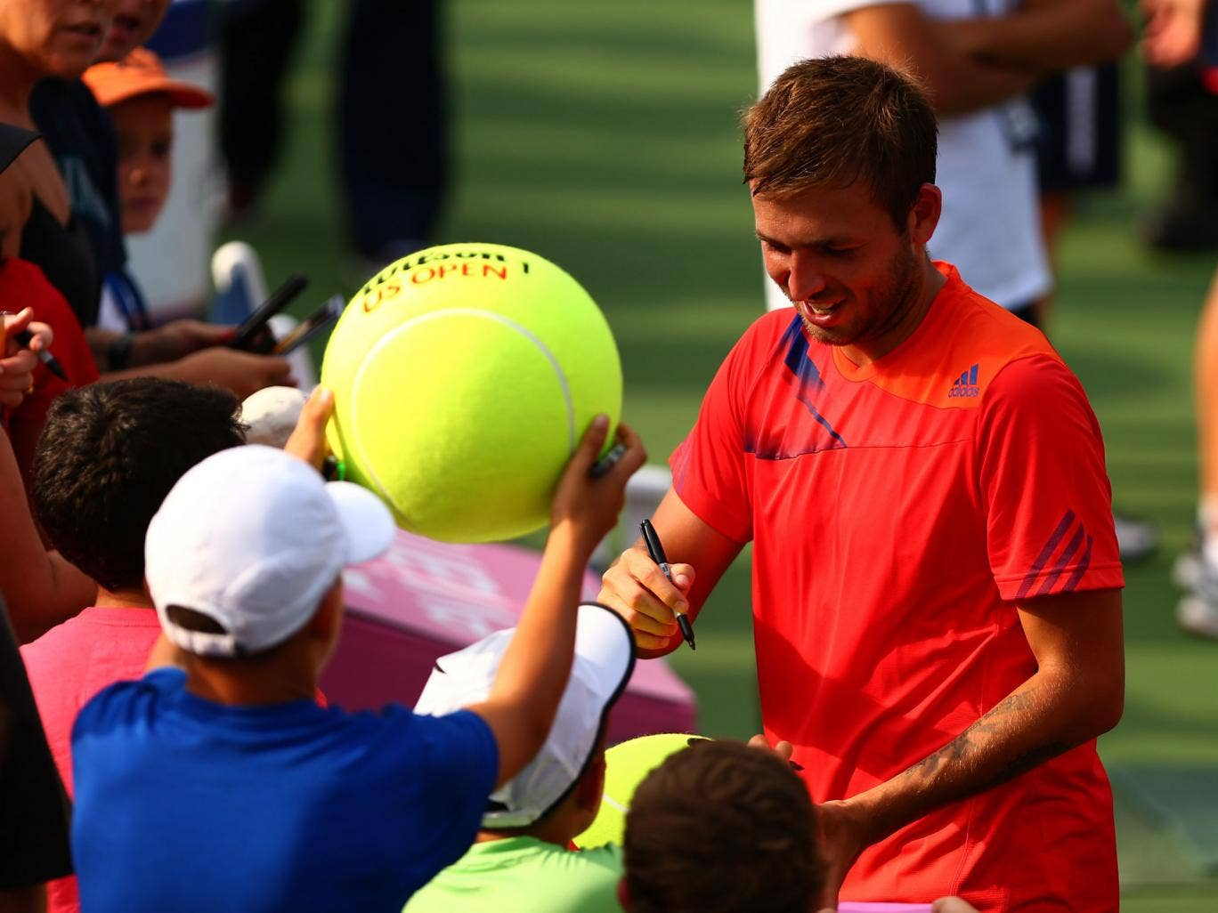 Dan Evans signs autographs after his shock victory over Bernard Tomic in New York