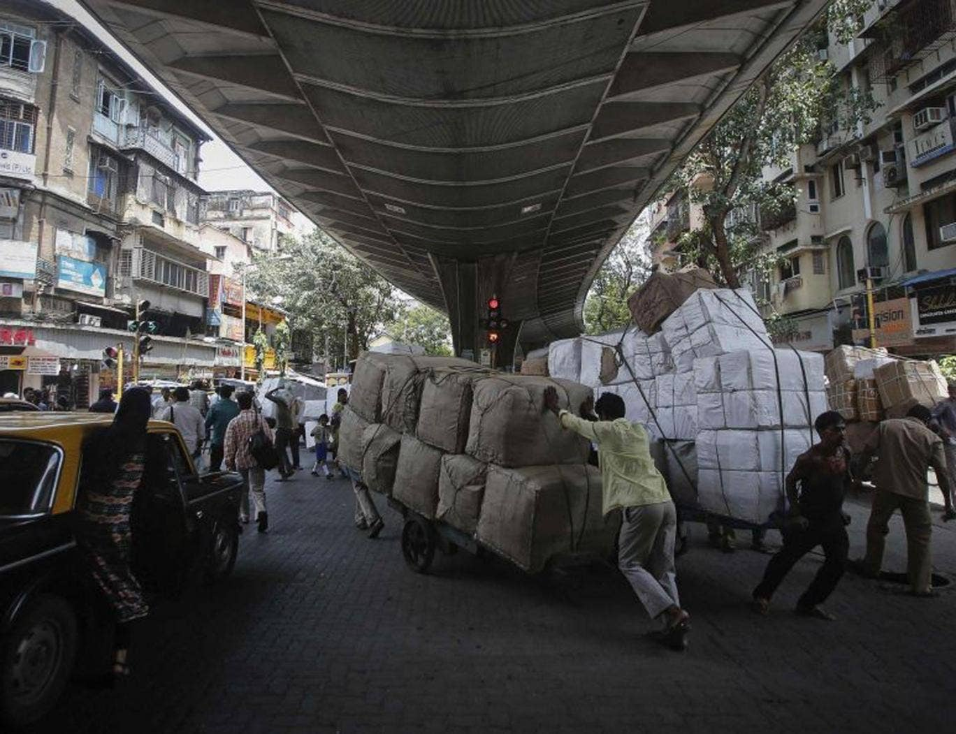 Laboueres move handcarts loaded with goods under a flyover at a market in Mumbai