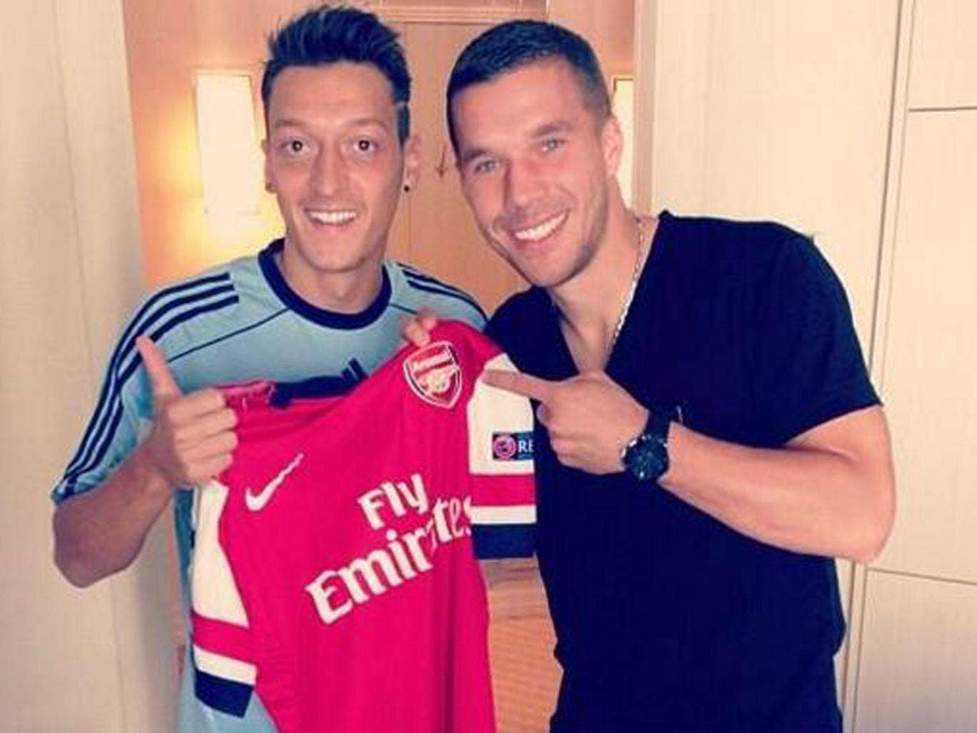 Mesut Ozil poses with new Arsenal team-mate Lukas Podolski while on duty with the Germany. Podolski, currently out with a hamstring injury, was being examined by the national team doctor