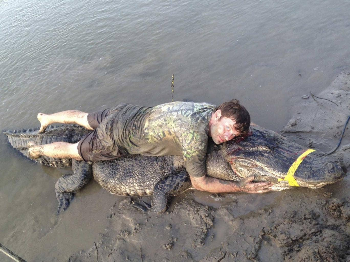 Dustin Bockman lies on top of his record-breaking alligator