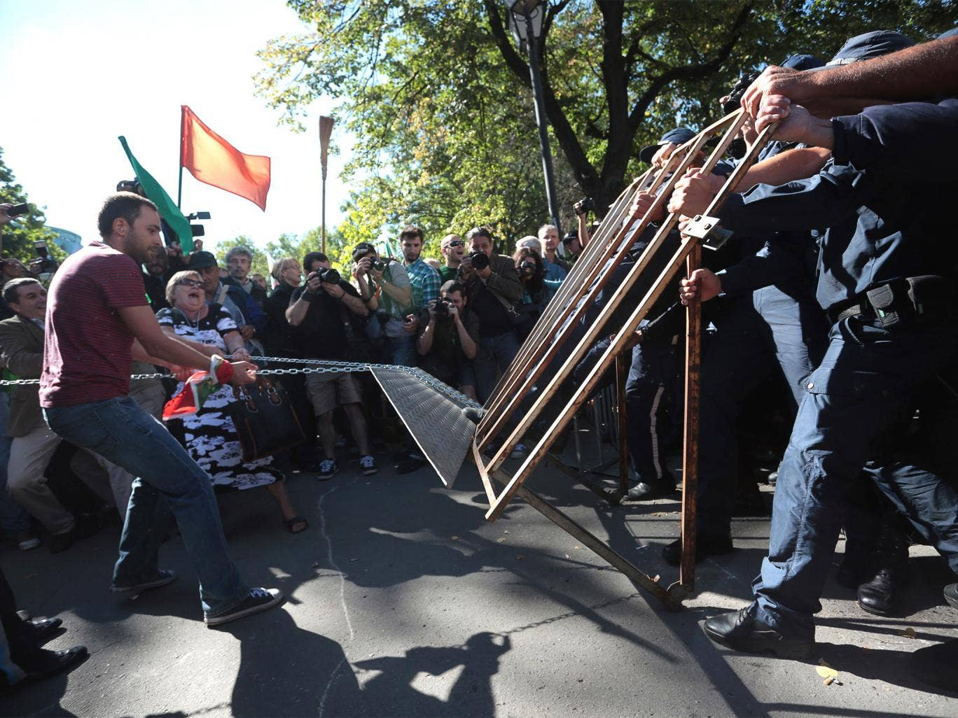 Protesters and police struggle over a fence near parliament