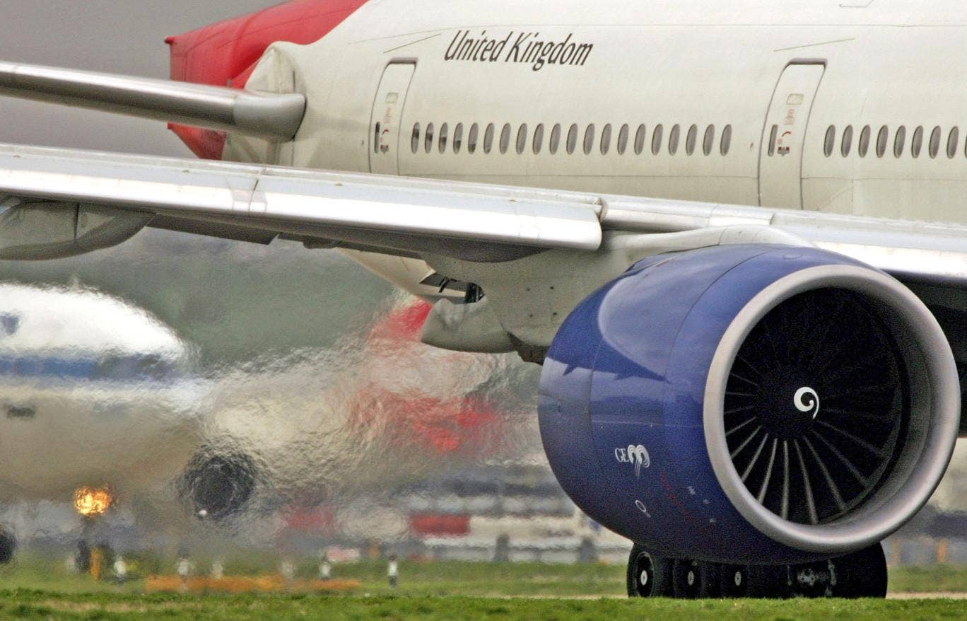 Exhaust emits from the engine of a passenger jet at Heathrow Airport
