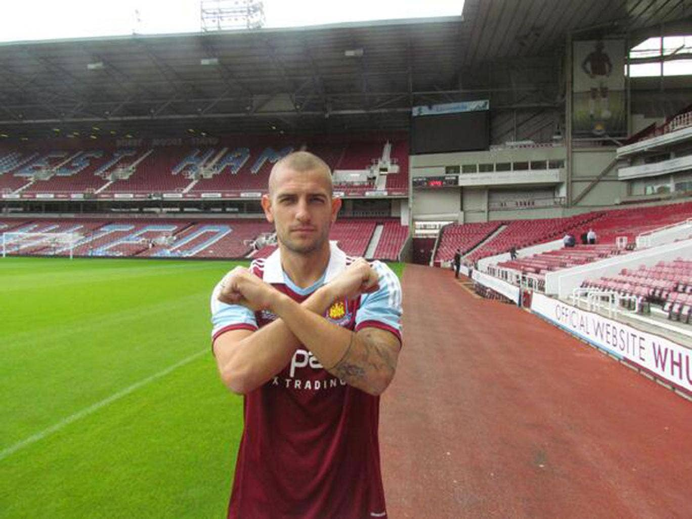 Mladen Petric poses in a West Ham shirt after completing his move to the Hammers