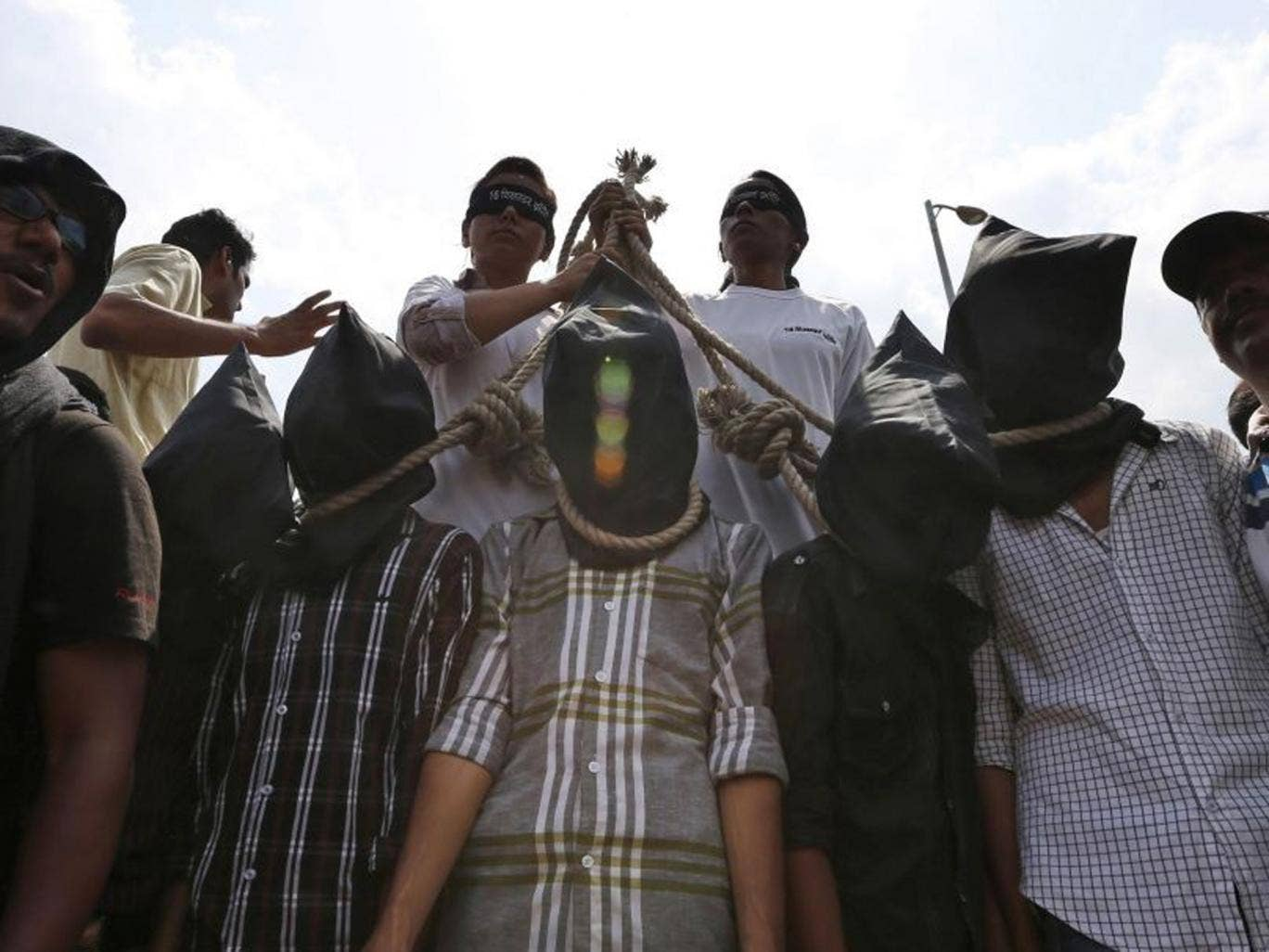 Indian protesters stage a mock hanging scene to demand death sentence for the four men found guilty of the gang-rape in Delhi