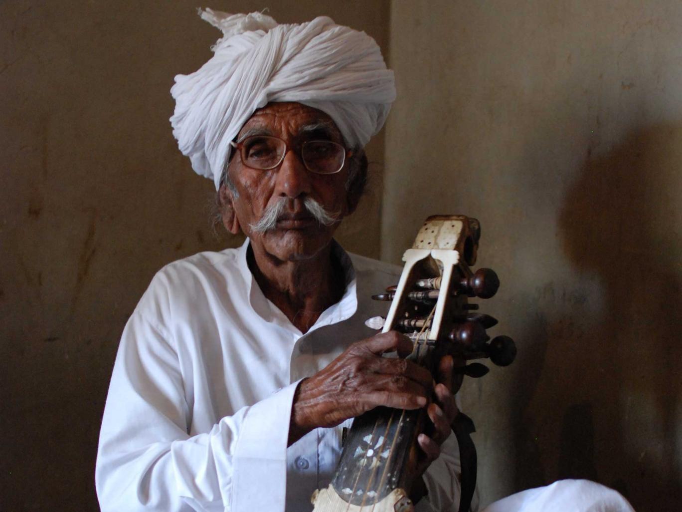 Sakar Khan at home with his kamancha
