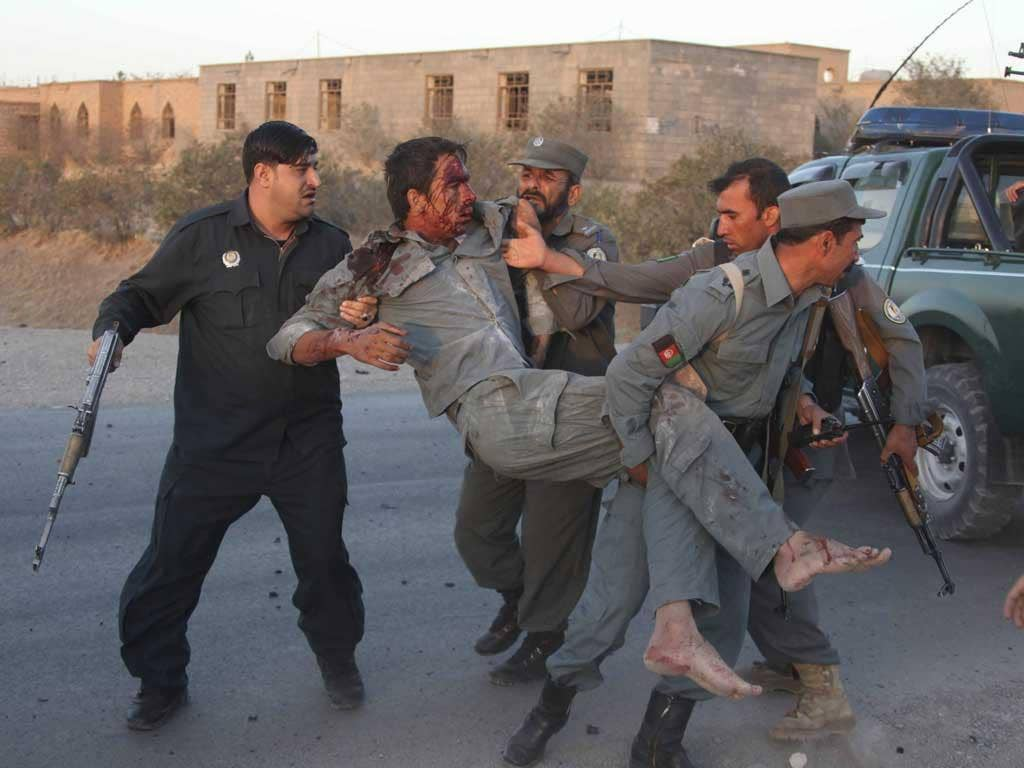 Afghan security personnel assist an injured police after the suicide car bombing and gunfight