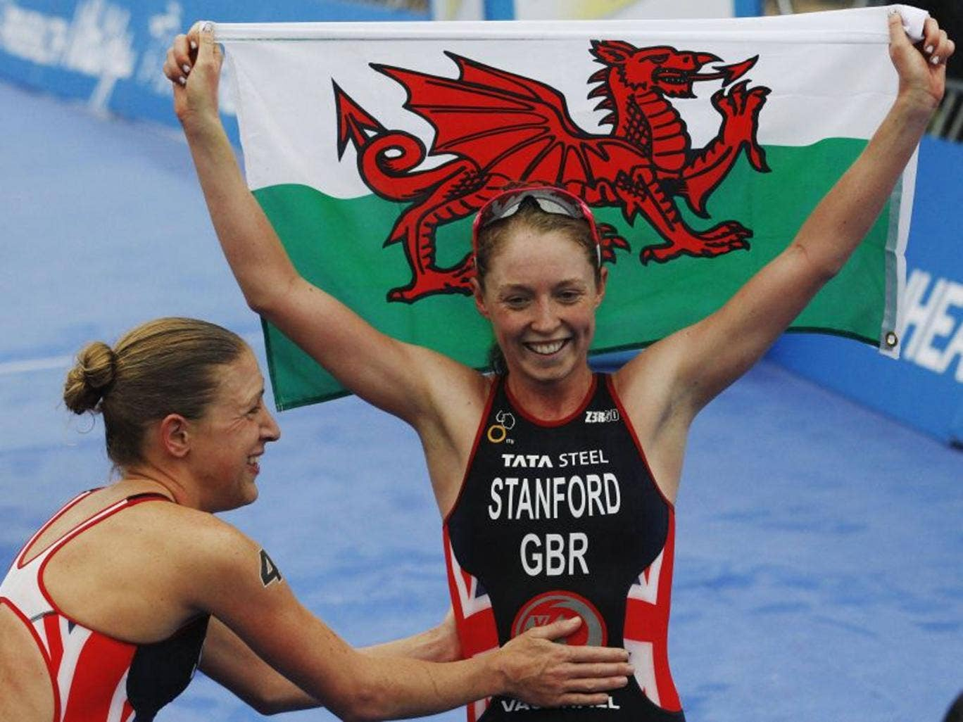 Golden girl: World champion Non Stanford raises the Welsh flag in triumph and gets a pat from silver medallist Jodie Stimpson