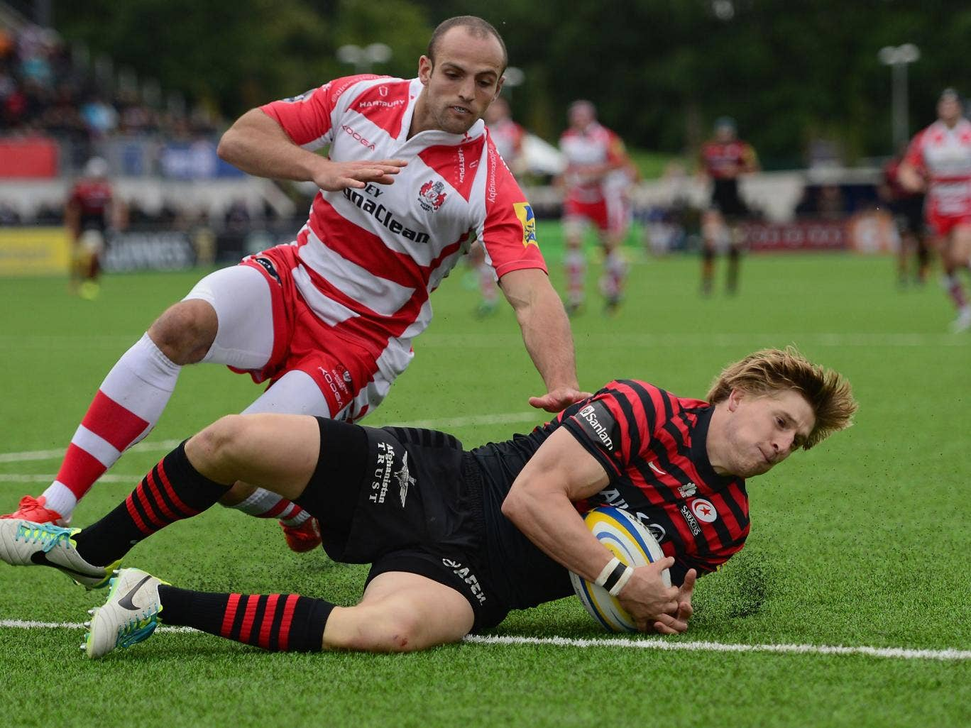 David Streetle of Saracens beats the tackle of Charlie Sharples of Gloucester to score a try
