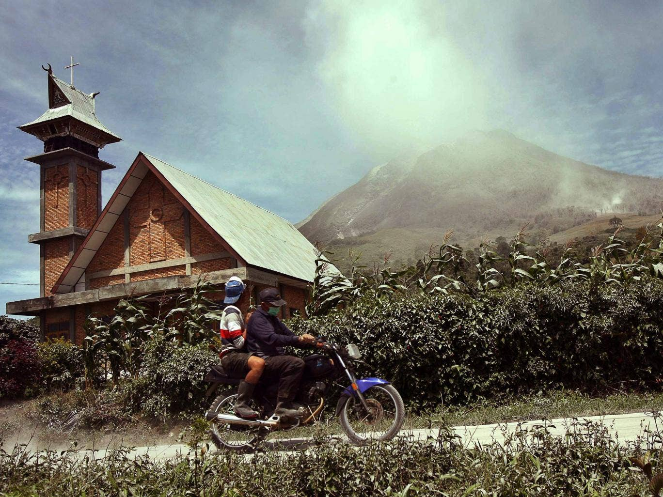 Indonesian villagers ride a motorbike as Mount Sinabung spews hot gas and ashes in the background during an eruption in Karo, North Sumatra province,  Indonesia