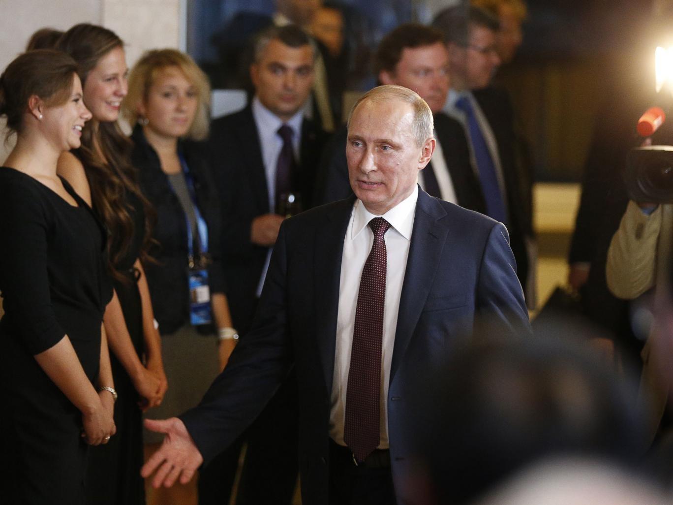Russian President Vladimir Putin gestures as he leaves the final plenary meeting of the Valdai International Discussion Club in the Novgorod Region