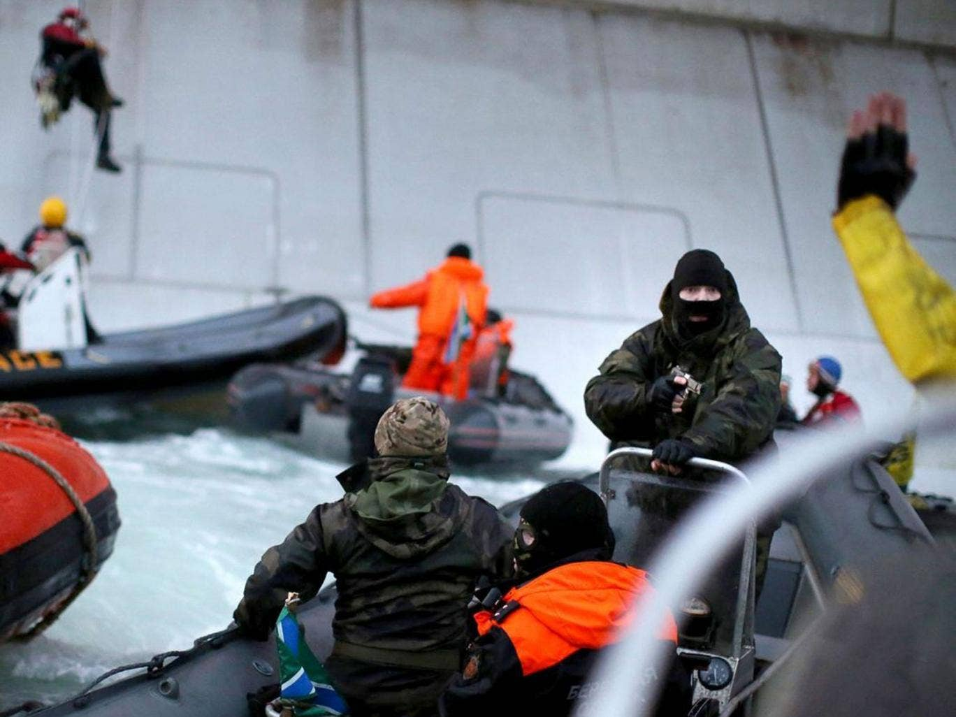 Greenpeace took this photo of a camouflaged officer from the Russian Coast Guard pointing a gun at an activist during an attempt to scale an Arctic oil rig on Wednesday