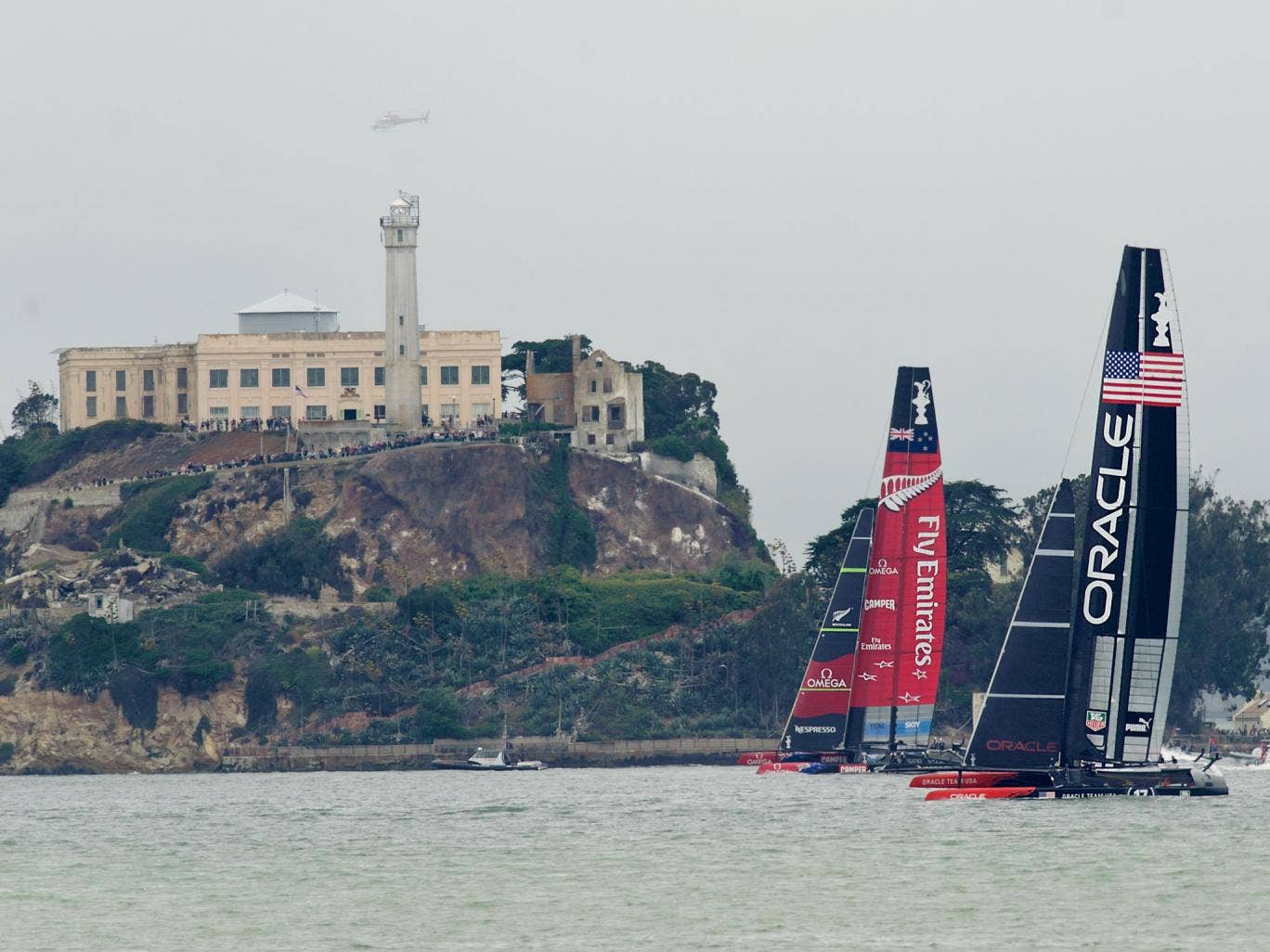 Passing Alcatraz Island in light wind, Emirates Team New Zealand and Oracle Team USA sail America's Cup race 13