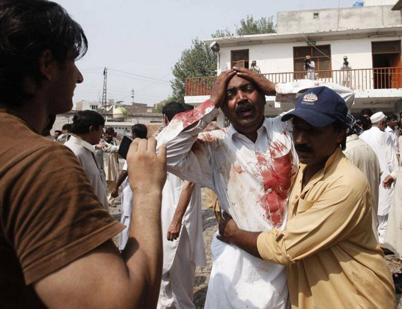 A man cries at the death of his brother at the blast site