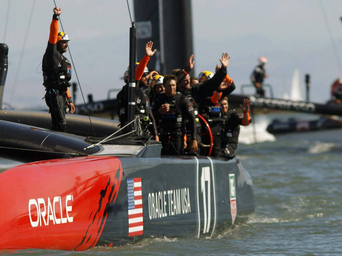 Crew members from Team USA wave to the crowd after defeating Emirates Team New Zealand during Race 15 in the 34th America's Cup yacht sailing race in San Francisco, California