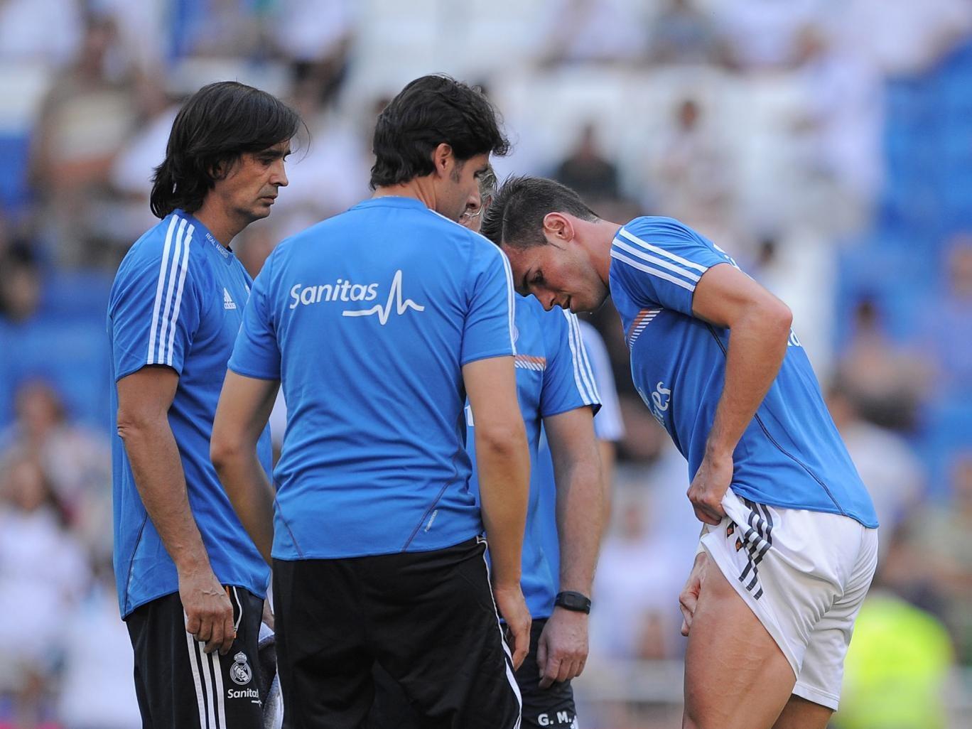 Gareth Bale assesses his injury at the Bernabeu