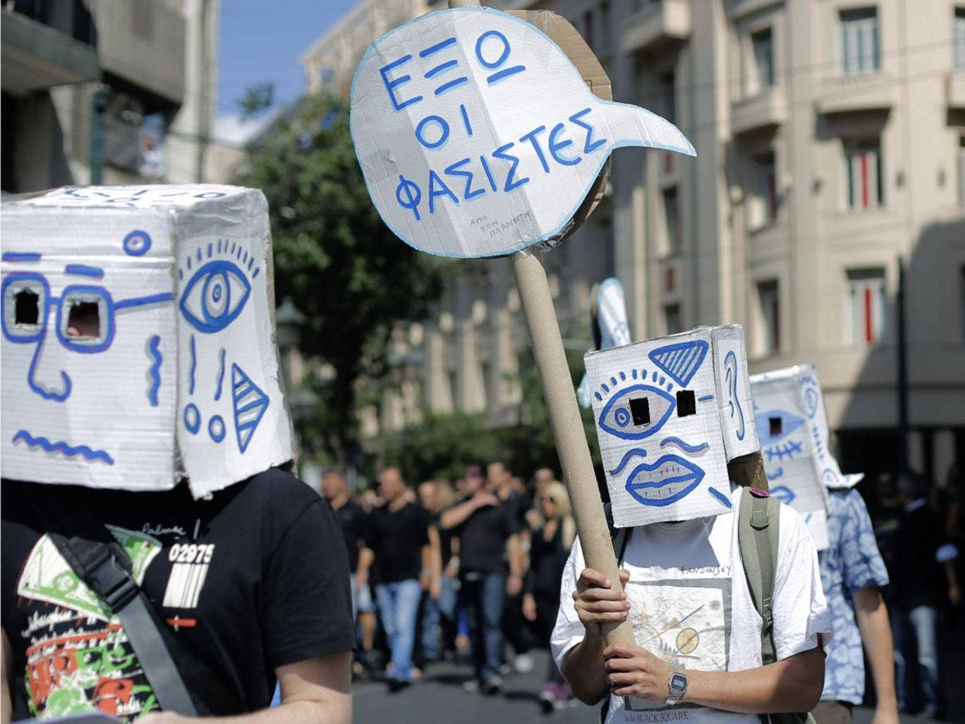 """Demonstrators carry a placard which reads """" Fascists Out """" during a protest in central Athens"""