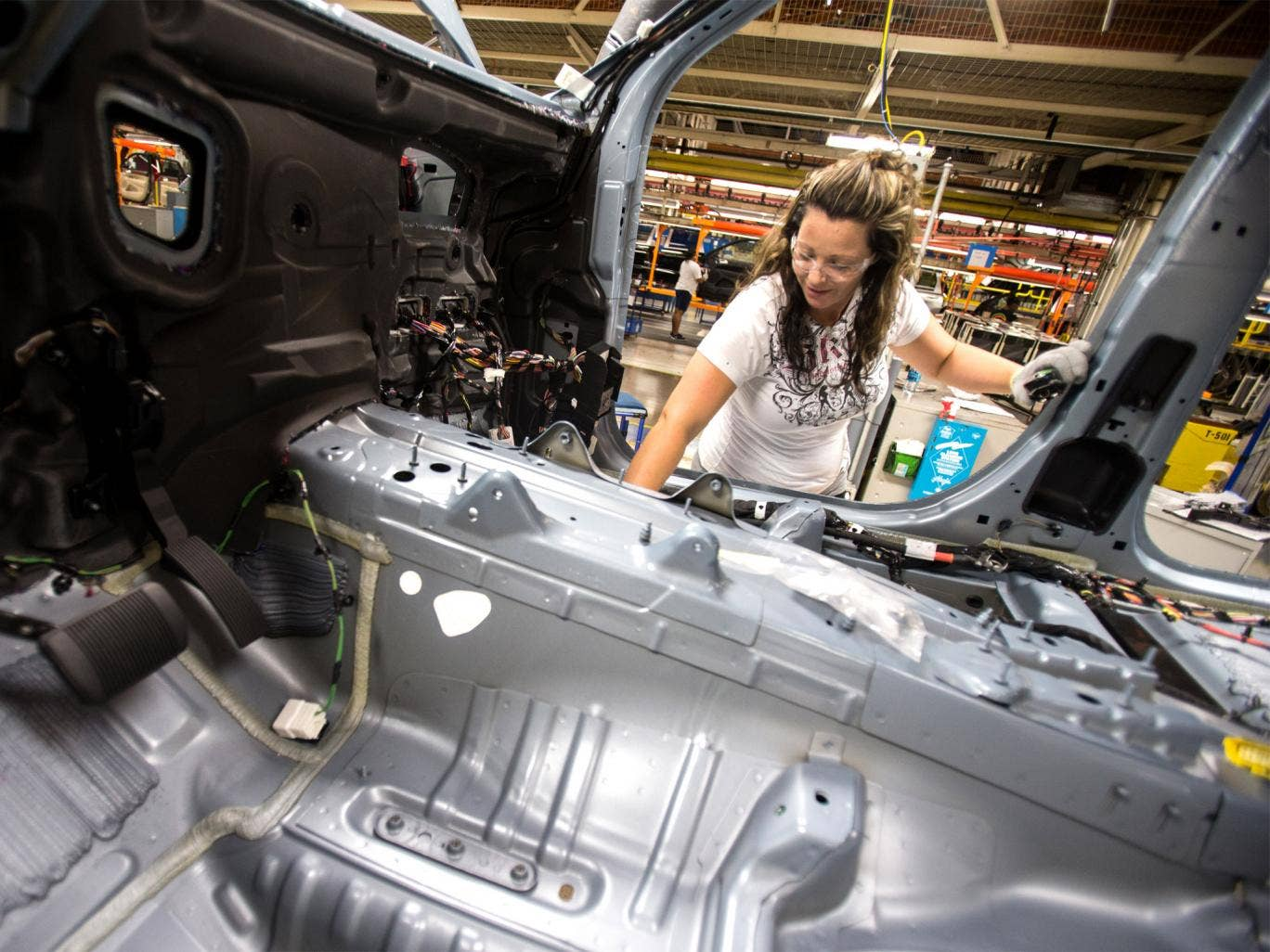 A worker at the Jefferson North plant inspects wiring on a Jeep, which has been one of the key drivers of Chrysler's turnaround