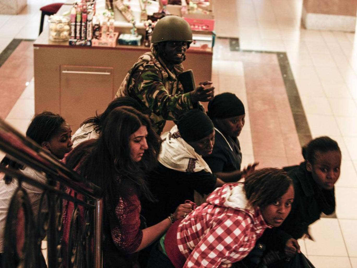 A soldier helps people inside Westgate mall on Saturday