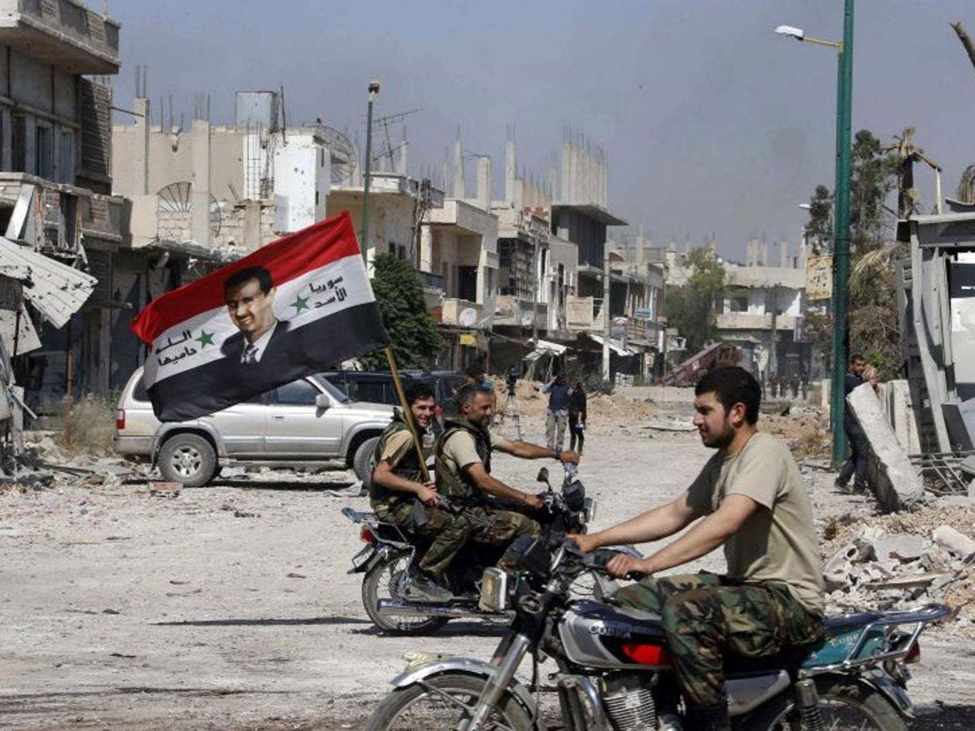 Flying the flag: Forces loyal to President Assad celebrate as the Syrian army take control in Qusair in June