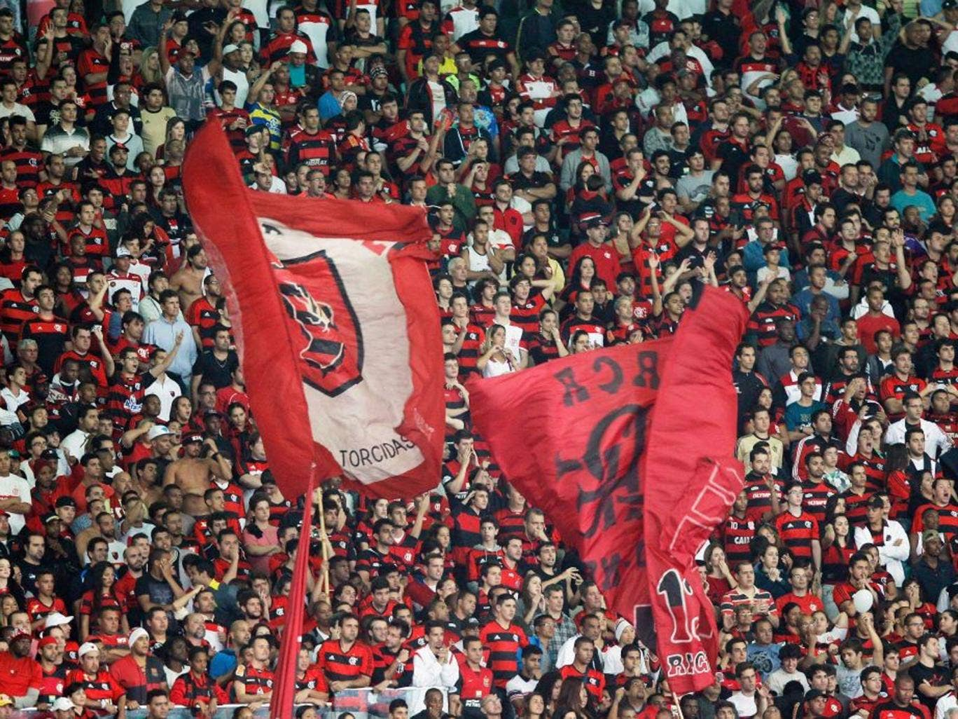 Flag of convenience: Supporters of Flamengo brandish their 'torcidas' banners for the match against Botafogo at the Maracana last week