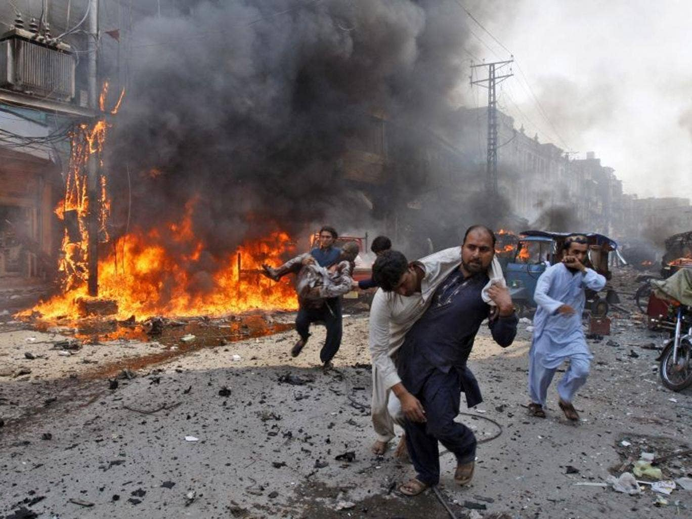 Injured Pakistani men are carried away from the site of a blast shortly after a car explosion in Peshawar, 29 September