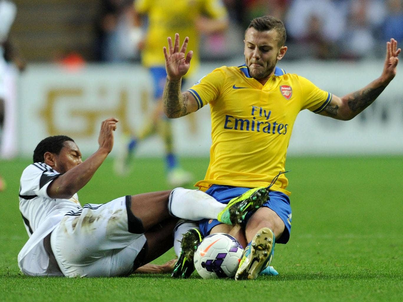 Jack Wilshere dives in on Jonathan De Guzman during Arsenal's clash with Swansea