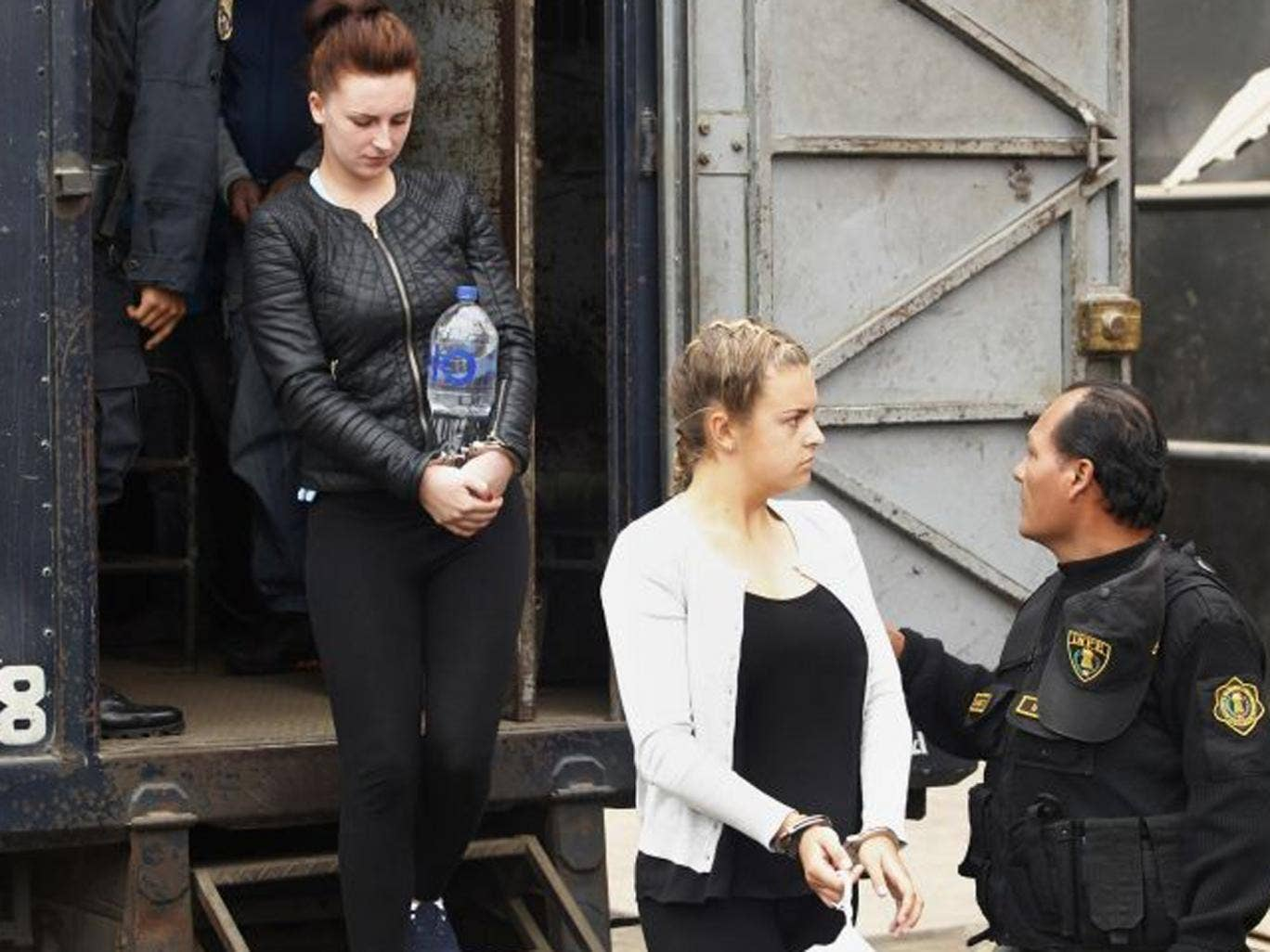 Melissa Reid (R) and Michaella McCollum Connolly are escorted by police at Sarita Colonia prison in Callao