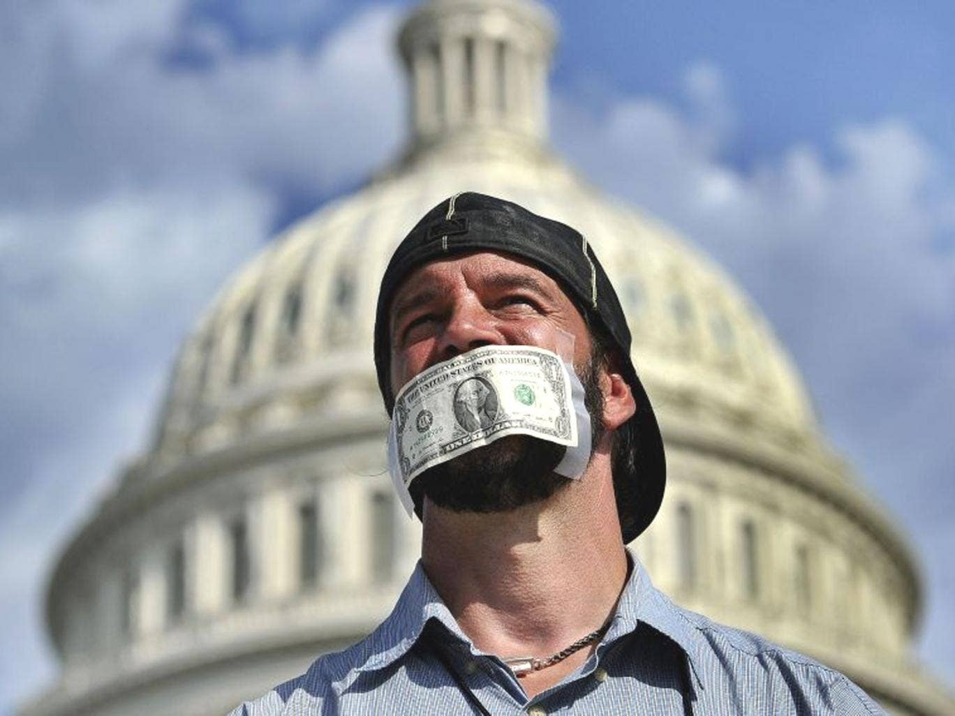 A protester covers his mouth with a dollar bill as he joins others in a demonstration in Washington, DC