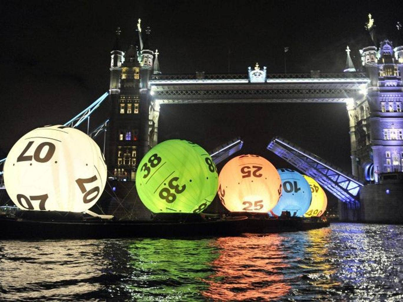 Camelot floats 26-ft Lotto balls down the Thames to celebrate new price system, with the cost of a ticket doubling