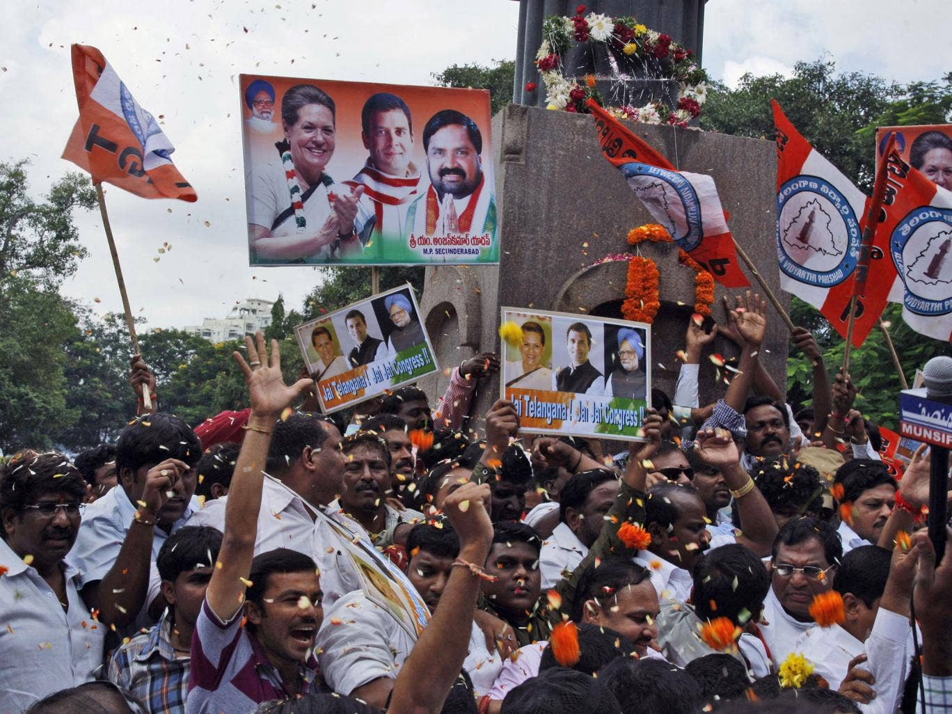 Indian Congress members and supporters celebrate after India's Union Cabinet approved the creation of a new state