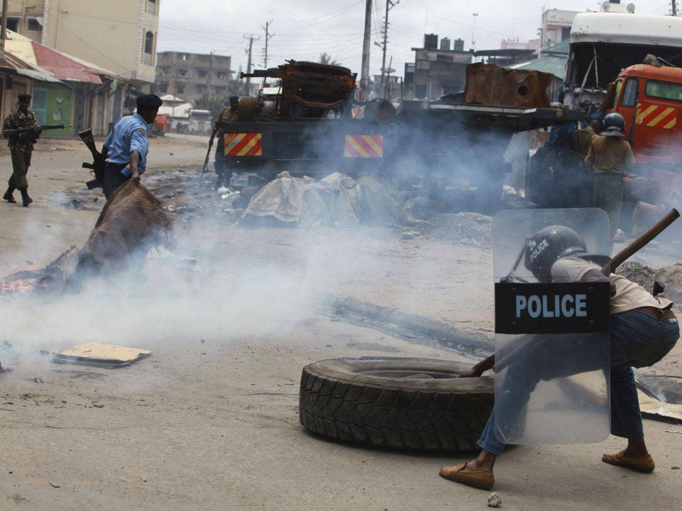 A police officer clears barricades erected by demonstrators during riots following the killing of an Islamic cleric at Kenya's coastal city of Mombasa