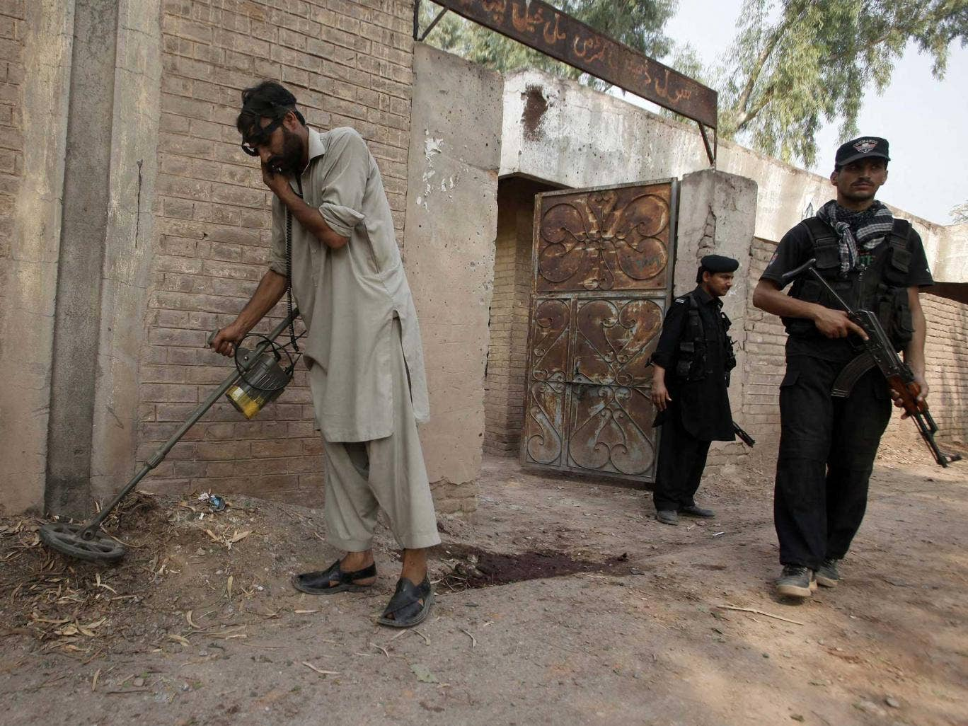 A security official uses a metal detector to survey the site of the bomb blast on the outskirts of Peshawar