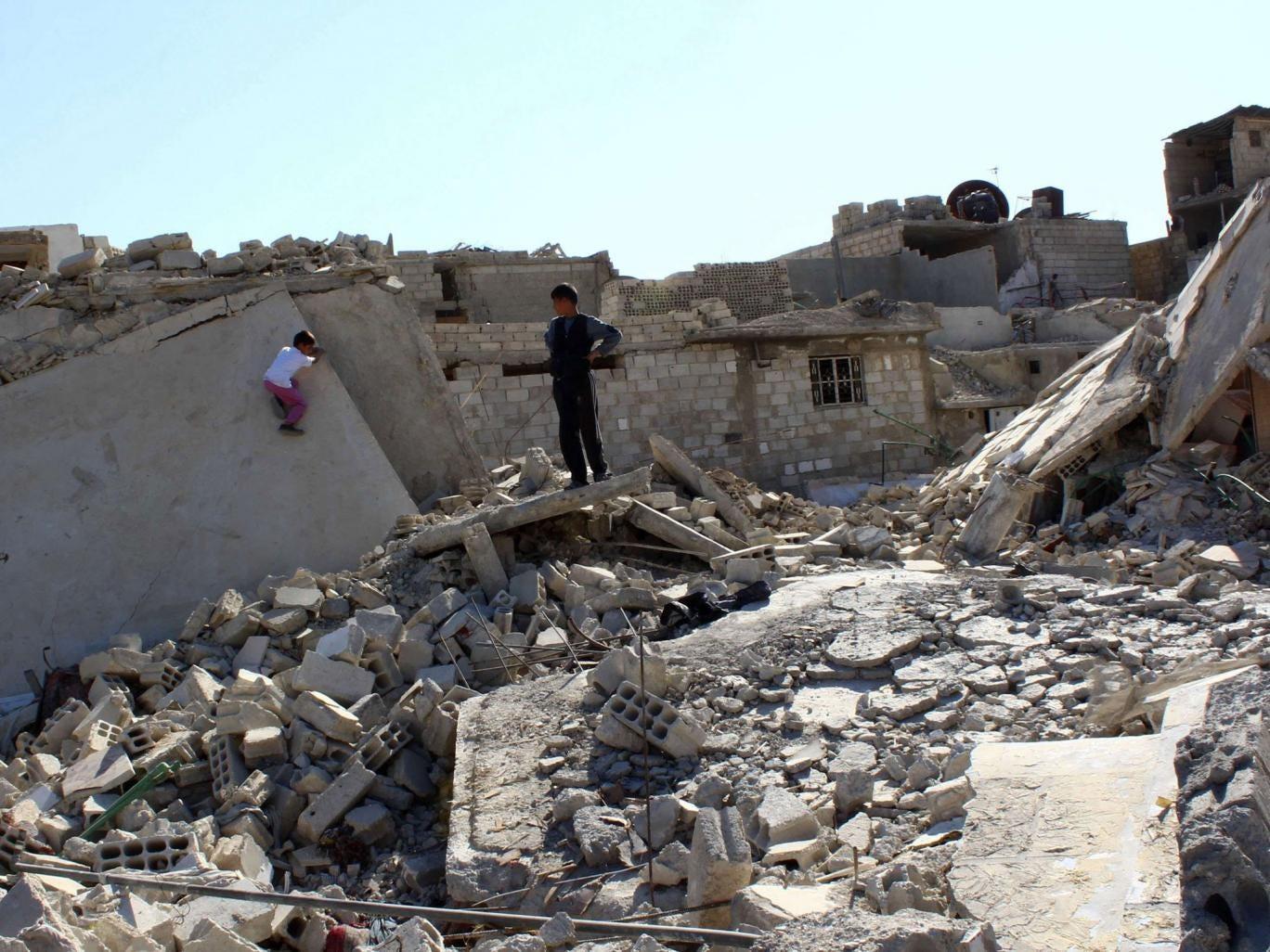 Boys play on debris from damaged buildings in the Duma neighbourhood in Damascus