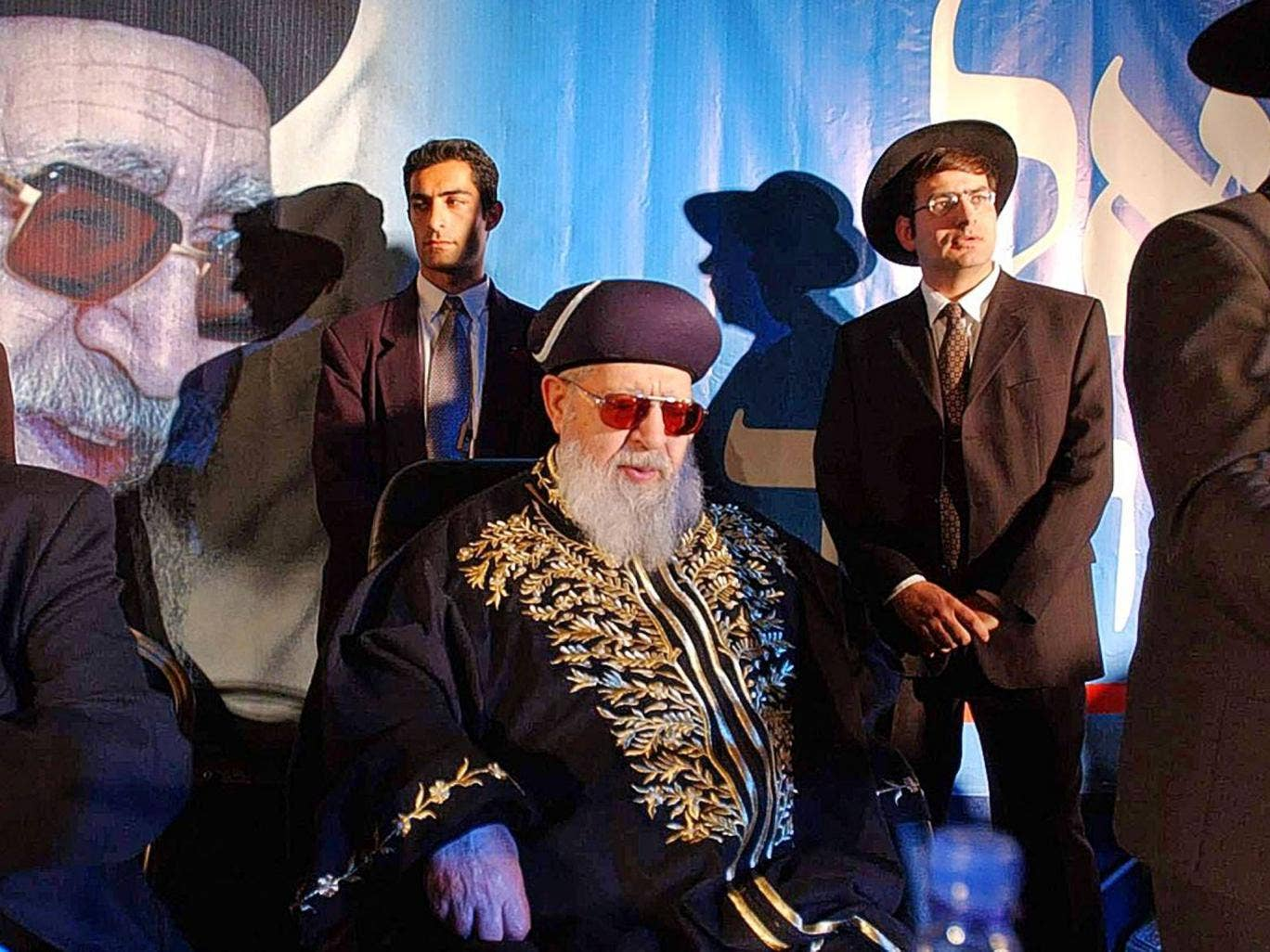 Yosef sits surrounded by Shas staff at a rally in 2002; he retained control over all party decisions